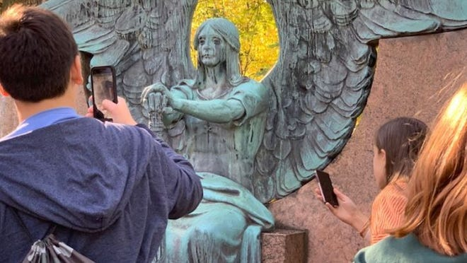 From left, Mark Pines, Lia Myroniak, and Arin Jensen photographing the Haserot Angel.