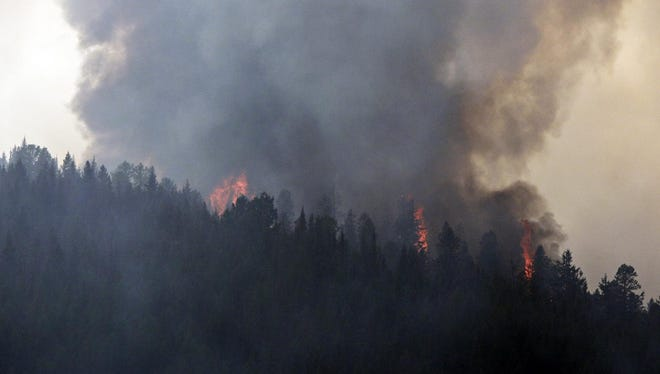 Smoke and flames from the the Sheep fire rise above the trees near Essex on Thursday.