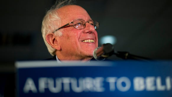 Bernie Sanders smiles while listening to a question