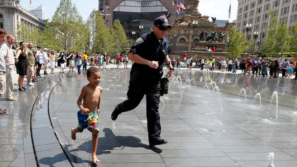 A Indiana State Police officer runs through a fountain