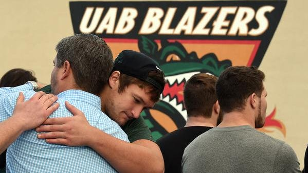 UAB offensive tackle Steve Pickern hugs UAB supporter Justin Craft  after UAB President Ray Watts announced the shut down of the UAB football program Tuesday, Dec. 2, 2014 in Birmingham, Ala. UAB is shutting down the football program after one of the Blazers' stronger seasons.  The university announced the decision Tuesday minutes after President Ray Watts met with the Blazers players and coaches, while several hundred UAB students and fans gathered outside for the third straight day in efforts to support the program. (AP Photo/AL.com, Joe Songer) MAGS OUT