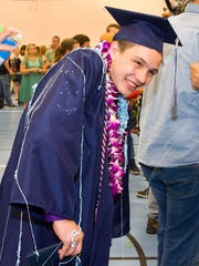 Graduating Senior Bret Silva is doused with silly string from his friends after the graduation ceremony.