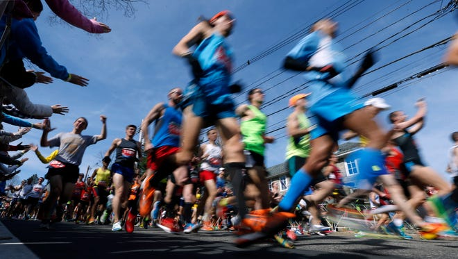 Runners leave the starting line of the 118th Boston Marathon Monday, April 21, 2014 in Hopkinton, Mass.