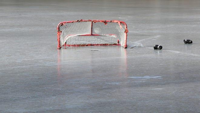 Hockey equipment sits stranded on ice.