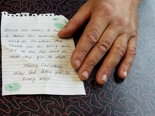 "Powers Diner owner John Liangos shows a note that'd been left over the weekend with $100. It states, ""Please use this money to buy a meal for somebody in need on Christmas day. Thank you for being open. If no one has need on that day, give to staff."""