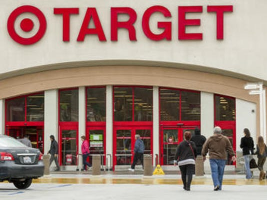 In this Dec. 19, 2013 file photo, shoppers arrive at a Target store in Los Angeles on Thursday, Dec. 19, 2013. Target reported a 16 percent drop in first-quarter earnings as a massive data breach and botched up expansion plans in Canada continue to batter