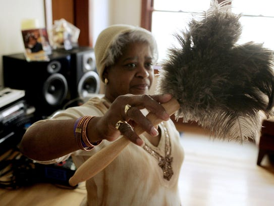 Maureen Yancey wields the feather duster used by her