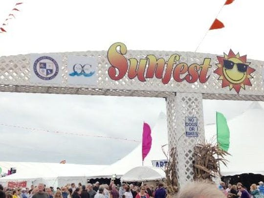 The Sunfest logo towers over the OC Inlet on Saturday, as thousands of resort visitors shopped at the annual festival for arts and crafts, gourmet food, clothes and accessories, and enjoyed live entertainment. Skies were overcast and winds gusted as high as 25 mph or higher, although rain held off during the day Saturday.