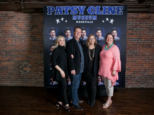 Museum founders Shannon Miller and Bill Miller, Nashville Mayor Megan Barry and Julie Fudge (Patsy Cline's daughter) stand in front of a poster for the Patsy Cline Museum.