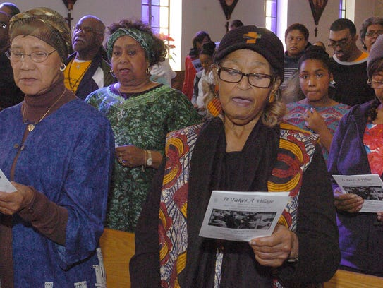 Opelousas residents stand up and sing a spiritual song