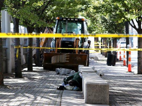 A person sleeps on the sidewalk on Third Street, between