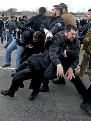Matthew Heimbach, top, leader of the white nationalist Traditional Workers Party, throws a protester to the ground.