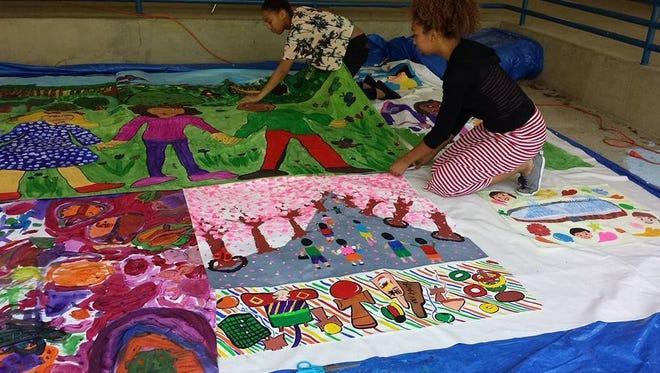 Children adding their artwork to a peace mural.