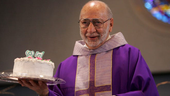 Monsignor Peter Lentine of St. Philomena in Detroit with his birthday cake after mass on Sunday April 2, 2006.