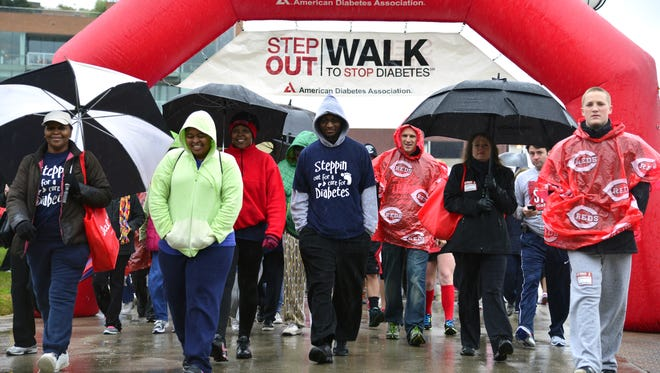 People brave a steady rainfall and cool temperatures to participate in a diabetes walk in 2013.