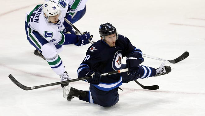Vancouver Canucks forward Jannik Hansen (36) trips Winnipeg Jets defenseman Jacob Trouba (8) during the second period at MTS Centre.