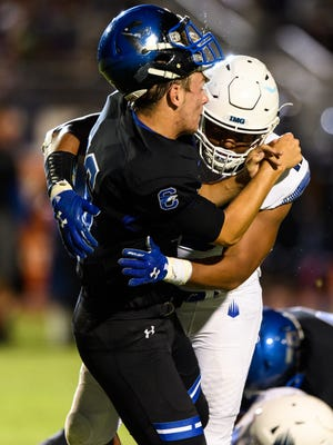 Chandler's Billy Bolger (#16) gets a late hit by IMG Academy's Xavier Thomas (#19) in the third quarter of their high school football game on Saturday, Aug. 26, 2017, at Chandler High School in Chandler, Ariz.