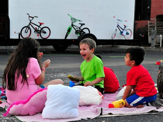Kids at Downtown Movie Night enjoy a friendly popcorn fight while waiting for the night's feature to begin.