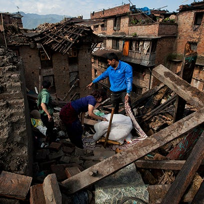 A Nepalese family collects belongings from their home