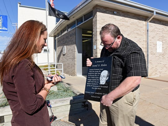 Ivend Holen's granddaughter Jennifer Harriel and author Robert Dudley view a plaque in memory of Holen during a dedication ceremony Tuesday, Oct. 18, at the Kimball Post Office. Holen was killed by a bomb at the post office in 1976.