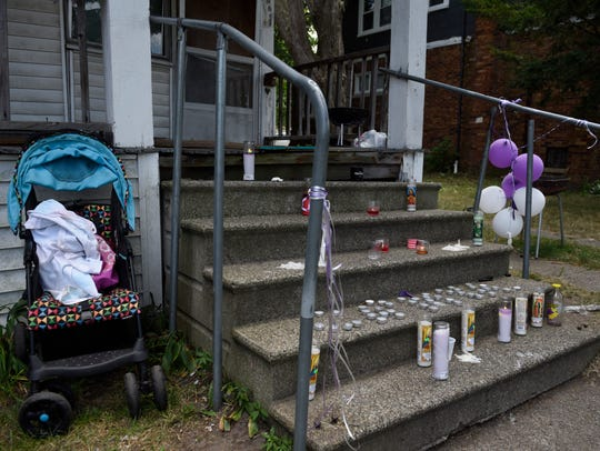 A baby stroller sits beside a makeshift memorial site