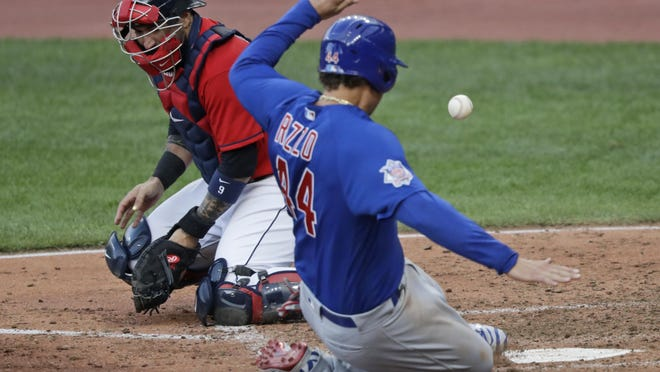 Chicago Cubs' Anthony Rizzo, right, scores as Cleveland Indians catcher Sandy Leon can't hold onto the ball in the fifth inning Wednesday in Cleveland.