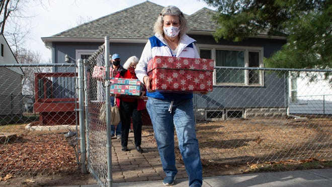 Jan Howard leads the way in delivering holiday boxes of food from the Topeka Civitan Club on Wednesday afternoon. The holiday boxes were created in lieu of the Civitan Club volunteering during the annual SLI holiday ball.
