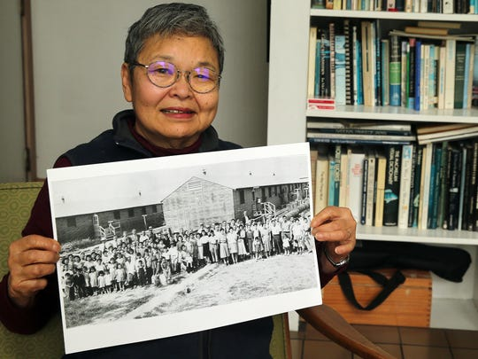 Mary Abo with a group picture of Block 6 at the Minidoka Internment Camp, where she and her family were housed during World War II, at her Bremerton home.