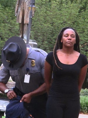 Bree Newsome is taken into custody after she removed the Confederate battle flag from a monument in front of the South Carolina Statehouse on Saturday. The flag was raised again by capitol workers about 45 minutes later.