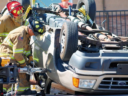 Alamogordo firefighters use the Jaws of Life to pry open the driver's side door of a Ford Ranger pickup after it was hit by a silver Pontiac car around 10 a.m. Monday.