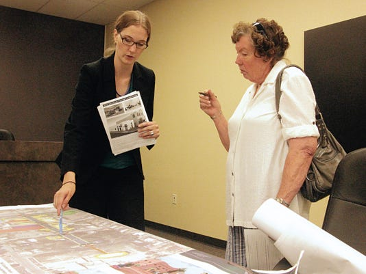 Hadley Yates goes over a map of Granado Street with a community member at the Greater Tularosa Foundation presentation Sunday evening.