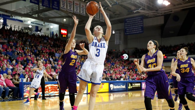Drake forward Lizzy Wendell (3) drives to the basket past Northern Iowa's Madison Weekly (2) and Ellie Herzberg (10) on Feb. 24 in Des Moines.