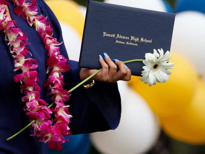 Graduates walk with their diplomas during a graduation