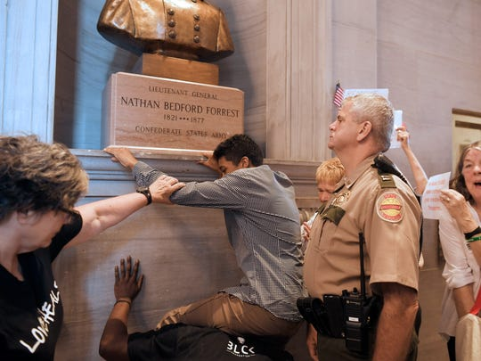 A protester tries to cover the bust of Nathan Bedford Forrest with fabric inside the Tennessee Capitol in Nashville on Aug. 14, 2017.