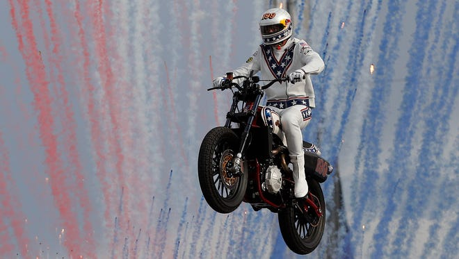 Travis Pastrana jumps a row of crushed cars on a motorcycle in Las Vegas.
