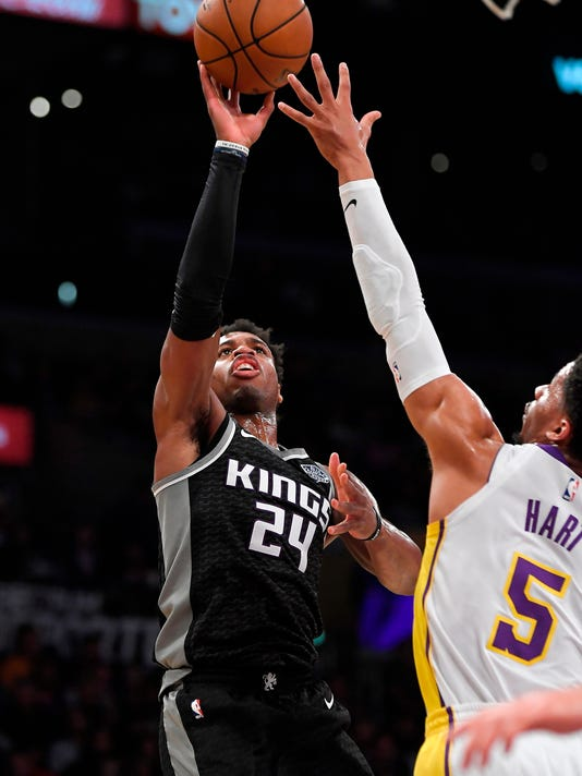 Sacramento Kings guard Buddy Hield, left, shoots as Los Angeles Lakers guard Josh Hart defends during the first half of an NBA basketball game Sunday, April 1, 2018, in Los Angeles. (AP Photo/Mark J. Terrill)