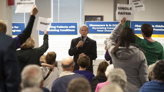 U.S. Rep. Tim Walberg, R-Mich., speaks as people stand in protest during a town hall meeting May 11, 2017, in Jackson, Mich.