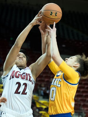 New Mexico State forward Tyler Ellis (22) fights for the rebound with Missouri-Kansas City's Aries Washington during third quarter action Thursday night at the Pan American Center.