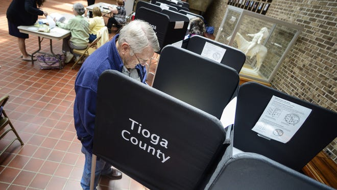 John Jones, from Owego, a retired Owego-Apalachin director of education, casts his vote in favor of the O-A budget in 2014 at the polling station at Owego Free Academy.