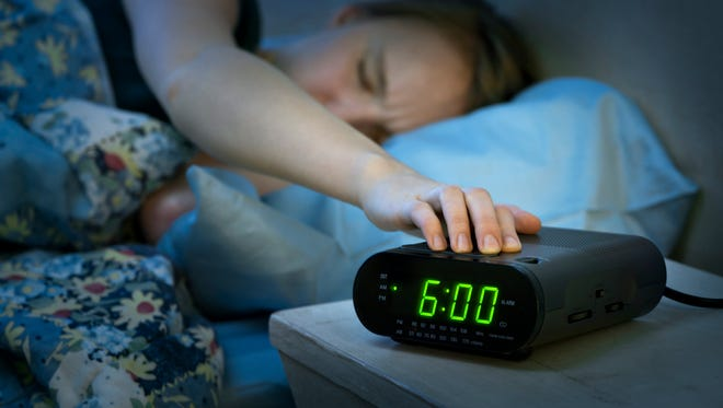 Woman waking up with an alarm clock.