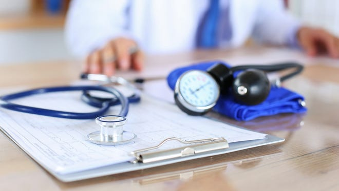 Medical stethoscope lying on cardiogram chart closeup.
