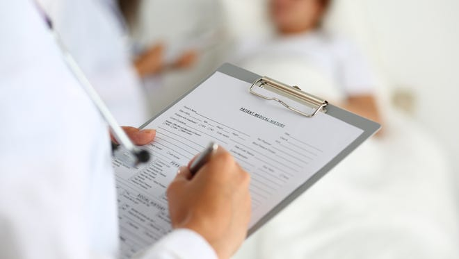 Doctor filling in patient medical history list
