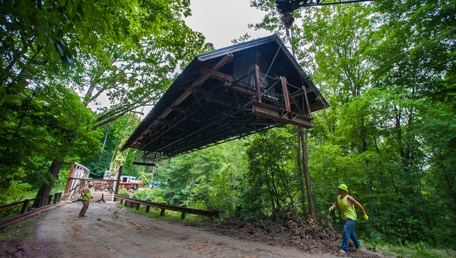 Nathan Cote of Morrisville, left, and Aaron Putvain of Hardwick from Blow & Cote guide the roof from the Seguin covered bridge in Charlotte after it was removed and lowered to the ground by two cranes on Wednesday, August 10, 2016.