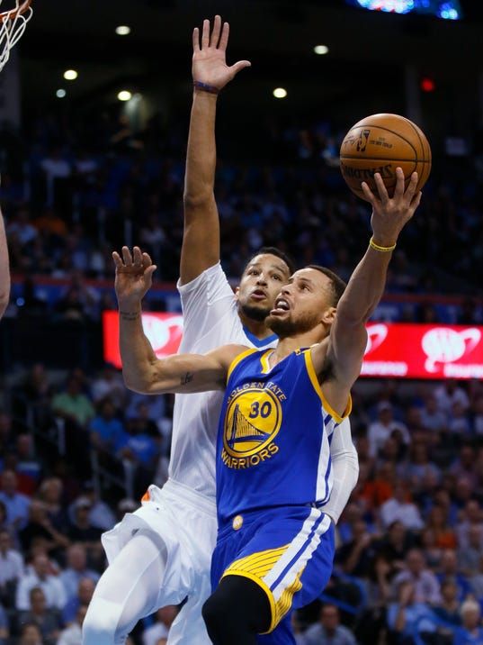 Golden State Warriors guard Stephen Curry (30) shoots in front of Oklahoma City Thunder forward Andre Roberson during the first quarter of an NBA basketball game in Oklahoma City, Monday, March 20, 2017. (AP Photo/Sue Ogrocki)