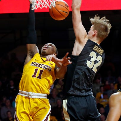 Minnesota's Isaiah Washington, left, is fouled by Purdue's
