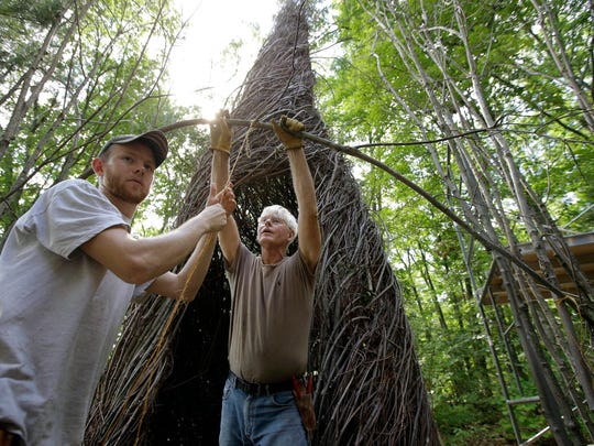 """In this Wednesday, Aug. 17, 2016 photo sculptor Patrick Dougherty, center, works with his son and assistant Sam Dougherty, left, as they construct a sculptural installation """"The Wild Rumpus,"""" from branches and sticks on the grounds of the Tower Hill Botanic Garden, in Boylston, Mass. Dougherty's installation opens to the public Thursday, Aug. 25."""