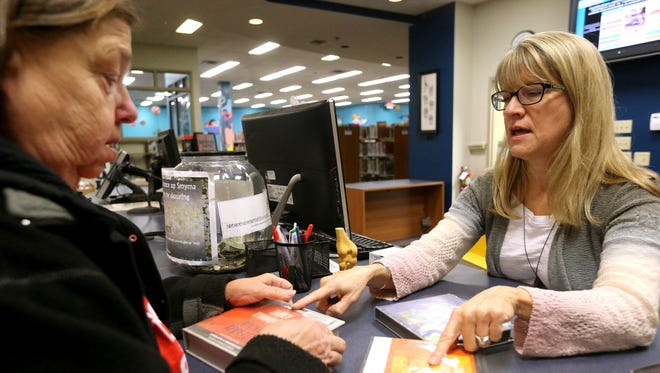 Lisa Robert, right, helps patron Donna Neverdosky determine the correct order for a series of books in this December 2015 photo at Linebaugh Public Library. The library will be renovated in the coming weeks and will close Aug. 25-29.