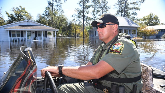 Erik Martin of the South Carolina Department of Natural Resources rides down Fork Retch Court in Mullins which has flooded since Hurricane Matthew hit the coast. Thursday, October 13, 2016.