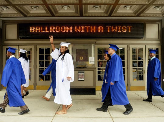 """Helen Thackston Charter School senior Zakiyia Hawkins waves to a passerby as she and her 33 classmates prepare to enter the Strand-Capitol Performing Arts Center for the school's inaugural graduation on Saturday. Helen Thackston opened its doors for the 2009-10 academic year. """"This is a historic occasion,"""" said co-salutatorian Daniel Felix before the ceremony."""