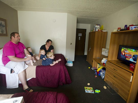 Nathan and Cassie Stocks watch TV in a hotel room with their sons (left to right) Ollie, Charlie and Henry. The family has been forced out of their home because of lead paint causing health issues for Charlie, their youngest child.
